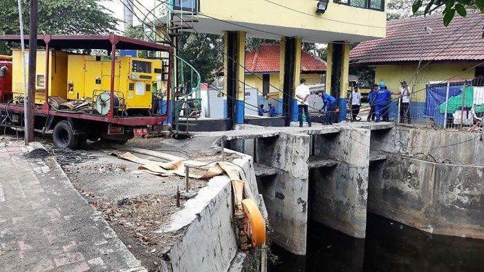 Petugas gabungan memompa air dari Kali Sentiong ke Kali Sunter tepatnya di Pintu Air Honda 1, Rabu (25/7/2018)