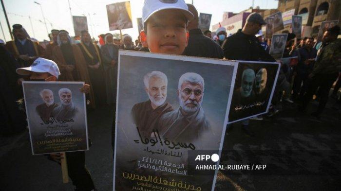 Seorang anak laki-laki Irak membawa potret komandan Irak Abu Mahdi al-Muhandis dan komandan Pengawal Revolusi Iran Qasem Soleimani selama demonstrasi di lingkungan Shoala barat Baghdad pada 1 Januari 2021, menuntut pengusiran pasukan AS dari Irak dan menyerukan balas dendam atas pembunuhan tersebut. al-Muhandis dan Soleimani, menjelang peringatan 3 Januari serangan drone AS. Pada 3 Januari, Irak akan menandai satu tahun sejak serangan pesawat tak berawak AS menewaskan komandan Irak Abu Mahdi al-Muhandis, wakil kepala jaringan paramiliter Hashed Al-Shaabi yang bersekutu dengan Teheran, bersama Soleimani, kepala operasi elit eksternal Iran. Pengawal Revolusi, hampir memicu konflik yang masih dikhawatirkan banyak orang.