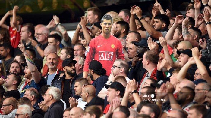 Potongan karton dari pemain baru Cristiano Ronaldo dipegang oleh pendukung Manchester United selama pertandingan sepak bola Liga Premier Inggris antara Wolverhampton Wanderers dan Manchester United di stadion Molineux di Wolverhampton, Inggris tengah pada 29 Agustus 2021.