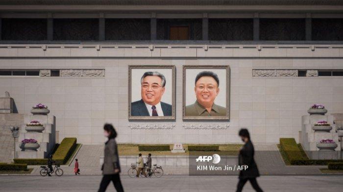 Orang-orang yang memakai topeng wajah berjalan di depan potret mendiang pemimpin Korea Utara Kim Il Sung dan Kim Jong Il (kanan) di Lapangan Kim Il Sung di Pyongyang pada 9 April 2020. (KIM Won Jin / AFP)
