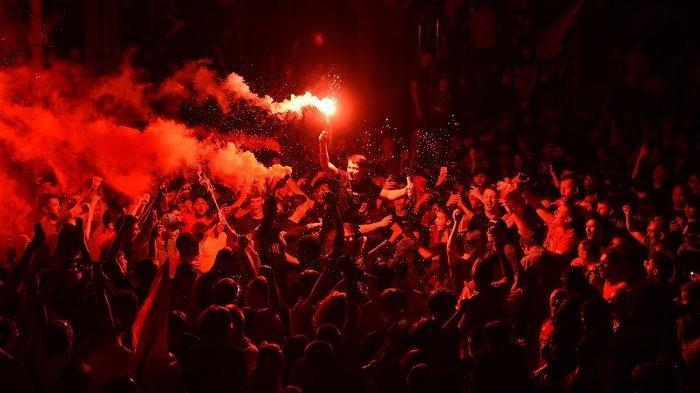 Fans merayakan Liverpool memenangkan gelar Liga Premier di luar stadion Anfield di Liverpool, barat laut Inggris pada 25 Juni 2020, menyusul kemenangan 2-1 Chelsea atas Manchester City. Liverpool dimahkotai juara Liga Premier tanpa menendang bola pada hari Kamis ketika kemenangan 2-1 Chelsea atas Manchester City mengakhiri 30 tahun menunggu The Reds untuk memenangkan gelar Inggris. Pasukan Jurgen Klopp memastikan gelar liga ke-19 untuk klub dengan rekor tujuh  OLI SCARFF / AFP