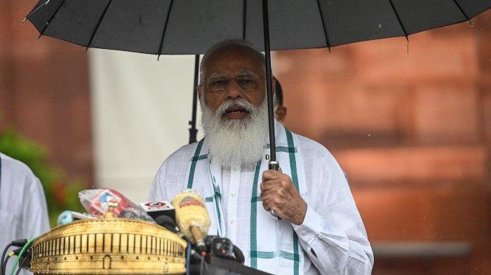 Perdana Menteri India Narendra Modi memegang payung saat hujan saat ia berbicara kepada perwakilan media setelah tiba untuk sesi monsun Parlemen di New Delhi pada 19 Juli 2021.