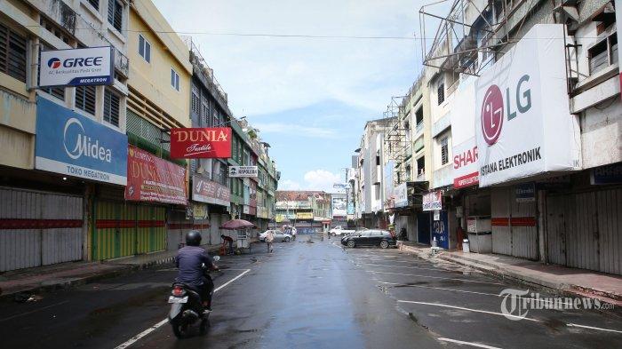 Warga melintas di antara pertokoan kawasan Pasar Tengah yang tutup pada hari pertama penerapan Pemberlakukan Pembatasan Kegiatan Masyarakat (PPKM) Darurat di Kota Bandar Lampung, Lampung, Senin (12/7/2021). Pemerintah setempat melakukan penerapan PPKM Darurat khususnya di wilayah Bandar Lampung mulai Senin ini hingga 20 Juli 2021 mendatang dan mewajibkan pusat perbelanjaan untuk menutup operasionalnya guna  memperketat aktivitas warga agar dapat menekan penyebaran virus Covid-19. Tribun Lampung/Deni Saputra