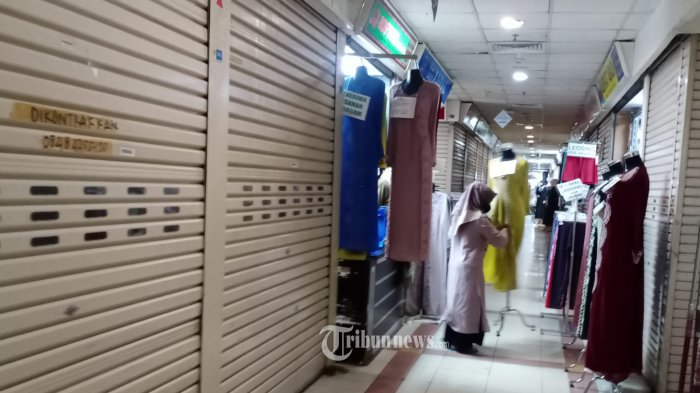 Suasana lenggang dan masih banyaknya toko yang tutup  pada hari pertama pelonggaran Pemberlakuan Pembatasan Kegiatan Masyarakat (PPKM) level 4 Pasar  Tanah Abang, Jakarta Pusat, Senin(26/7/2021). Pusat tekstil terbesar se-Asia Tenggara ini mulai kembali beroperasi dari pukul 07.00-15.00 dengan menyiagakan sekitar 750 petugas untuk menjaga kedisiplinan protokol kesehatan untuk mencegah penularan COVID-19. WARTA KOTA/HENRY LOPULALAN