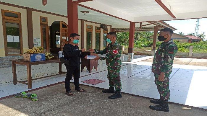 Prajurit Yonkav 12/BC bagikan masker gratis kepada masyarakat Desa Peniti Luar, Kecamatan Siantan, Kabupaten Mempawah, Kalimantan Barat, Jumat (4/6/2021).