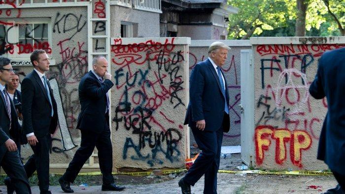 Presiden AS Donald Trump berjalan melewati tembok yang dicoret-coret pendemo ketika menuju Gereja Episkopal St John's yang lokasinya tak jauh dari Gedung Putih.