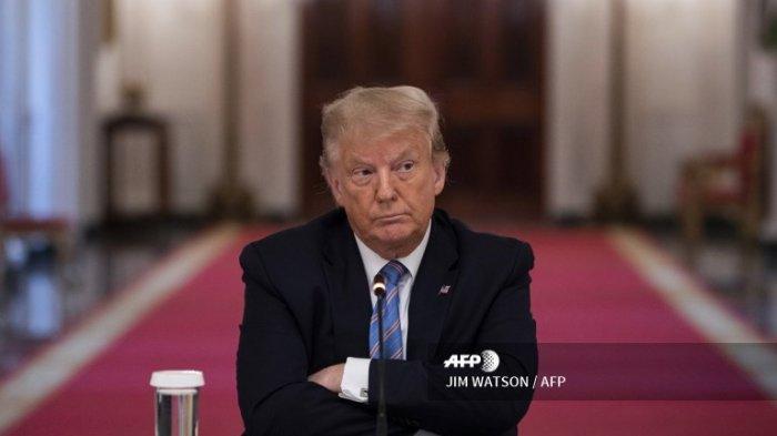 Presiden AS Donald Trump duduk dengan tangan bersilang saat diskusi meja bundar tentang Pembukaan Kembali Sekolah-Sekolah Amerika yang Aman selama pandemi, di Ruang Timur Gedung Putih pada 7 Juli 2020, di Washington, DC.