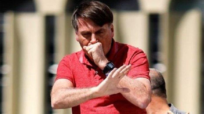 Presiden Brasil Jair Bolsonaro terlihat batuk ketika menghadiri demonstrasi menentang lockdown Covid-19 di Brasilia, 19 April 2020.