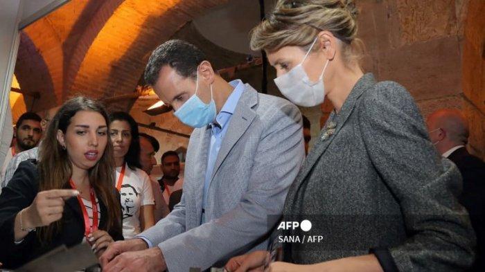 Sebuah gambar selebaran yang dirilis oleh Kantor Berita Arab Suriah (SANA) resmi pada 4 November 2020 menunjukkan Presiden Suriah Bashar al-Asad dan istrinya Asma, mengenakan masker wajah karena pandemi Covid-19, selama kunjungan ke sebuah tempat yang disponsori negara dalam pameran di Damaskus untuk bisnis kecil dari Aleppo, Suriah utara.