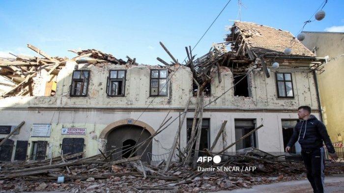 Seorang pria berjalan di samping puing-puing dan bangunan yang rusak di Petrinja, sekitar 50 km dari Zagreb, setelah kota itu dilanda gempa berkekuatan 6,4 pada 29 Desember 2020.