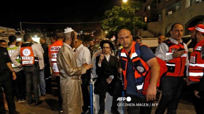 Petugas medis mengevakuasi seorang pria Yahudi ultra-Ortodoks yang terluka setelah runtuhnya tribune tempat duduk di sebuah sinagoge di pemukiman Israel di Givat Zeev di Tepi Barat pada 16 Mei 2021.