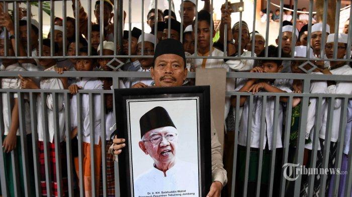 Keluarga membawa foto jenazah Alm KH Sholahuddin Wahid saat akan dimakamkan, Senin (3/2/2020). Ulama yang biasa disapa Gus Sholah tersebut meninggal di RS Harapan Kita, Jakarta, setelah menderita sakit. SURYA/AHMAD ZAIMUL HAQ