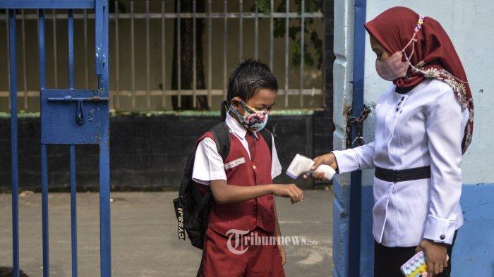 Seorang guru mengecek suhu tubuh siswa yang akan mengikuti Pengajaran Tatap Muka (PTM) hari pertama di SDN 232, Palembang, Senin (6/9/2021). Siswa dan guru menerapkan protokol yang ketat seperti selalu memakai masker, melakukan pengecekan suhu tubuh dan mencuci tangan sebelum masuk ke dalam kelas. Siswa pun diatur untuk mengikuti pembelajaran tatap muka sebanyak seminggu dua kali pertemuan dengan durasi dua jam pelajaran.TRIBUN SUMSEL/ABRIANSYAH LIBERTO