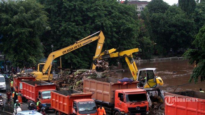 Alat berat mengangkat sampah yang tersangkut di jembatan Sungai Ciliwung di kawasan Kampung Melayu, Jakarta Timur, Rabu (1/1/2020). Puluhan ribu kubik sampah terus diangkat dari tengah derasnya arus Sungai Ciliwung agar aliran air lancar sehingga tidak meluap dan menambah parah banjir di Jakarta yang diakibatkan oleh curah hujan yang tinggi. Warta Kota/Henry Lopulalan