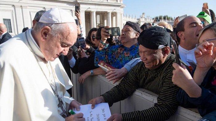 Paus Fransiskus menandatangani Berkat Damai untuk Bangsa Indonesia yang disodorkan AM Putut Prabantoro dalam audiensi umum di Lapangan Santo Petrus, Vatikan, Rabu (16/10/2019)