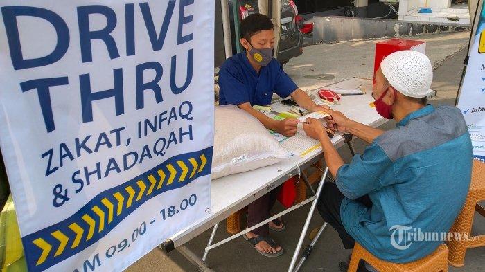 Pengendara bermotor membayar zakat fitrah kepada petugas lewat layanan Drive Thru Zakat, Infaq, dan Shadaqah yang diselenggarakan Pusat Zakat Umat (PZU) Persatuan Islam (Persis) di pinggir jalan depan Masjid PP Persis, Jalan Perintis Kemerdekaan (Viaduct), Kota Bandung, Jawa Barat, Senin (10/5/2021). Layanan pembayaran zakat secara Drive Thru ini dilakukan guna memberikan kemudahan dan kecepatan kepada muzakki yang akan membayar zakat fitrah di saat pandemi Covid-19. Layanan ini dimulai pada 14 hari terakhir hingga malam takbiran. Disamping itu PZU Persis juga menerima layanan zakat, infaq, dan shadaqah panggilan ke rumah.