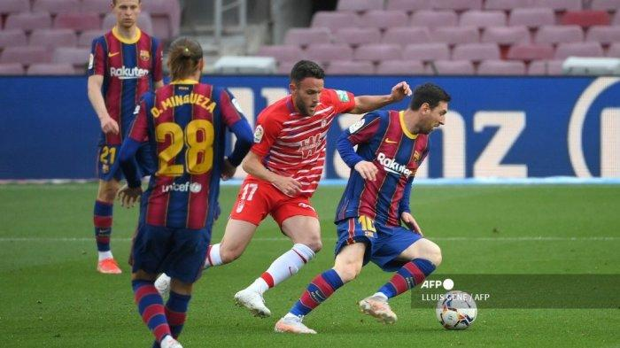 Bek Spanyol Granada Quini (tengah) menantang pemain depan Argentina Barcelona Lionel Messi selama pertandingan sepak bola Liga Spanyol antara Barcelona dan Granada di stadion Camp Nou di Barcelona pada 29 April 2021. LLUIS GENE / AFP