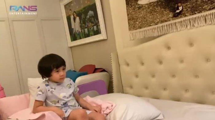 Rafathar tengah asyik menyusun bantal dan gulingnya menjadi selayaknya sebuah kursi.