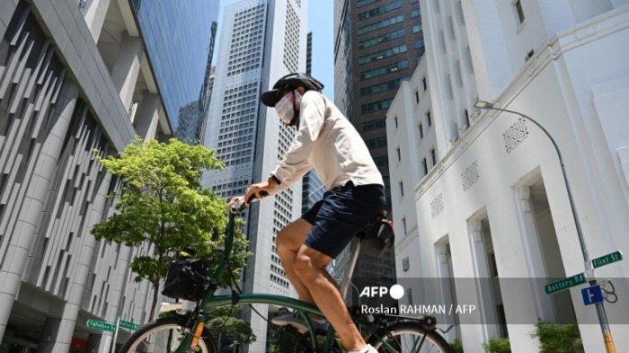 Seorang pria mengendarai sepeda di sepanjang jalan di kawasan bisnis keuangan Raffles Place di Singapura pada tanggal 20 April 2021.