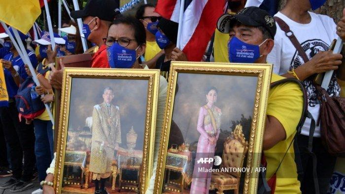 Pengunjuk rasa royalis memegang foto Raja Thailand Maha Vajiralongkorn (kiri) dan Ratu Suthida di Bangkok pada 16 Agustus 2020, menjelang protes anti-pemerintah di ibu kota Thailand.