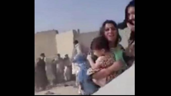 Seorang ibu melindungi bayinya dari tembakan Taliban di luar Bandara Kabul. (Sumber: Mirror)