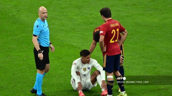 Bek Prancis Raphael Varane (tengah) bereaksi di sebelah kiper Inggris Anthony Taylor (kiri) setelah cedera saat pertandingan final Liga Bangsa-Bangsa antara Spanyol dan Prancis di stadion San Siro di Milan, pada 10 Oktober 2021.