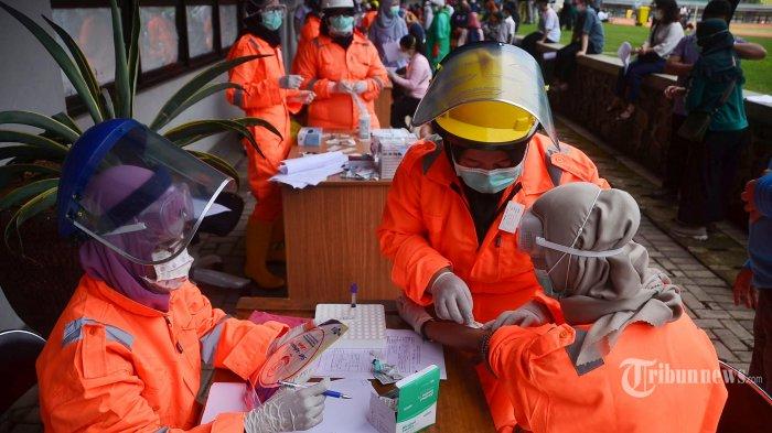 Petugas kesehatan melakukan rapid test Covid-19 massal di Stadion Patriot, Bekasi, Jawa Barat, Rabu (25/3/2020). Rapid test massal tersebut dilakukan terhadap orang-orang yang berisiko tinggi terpapar dan dimaksudkan untuk mengidentifikasi penyebaran virus corona atau Covid-19. AFP/Rezas