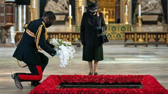 Ratu Inggris Elizabeth II memandang Equerry-nya, Letnan Kolonel Nana Kofi Twumasi-Ankrah (kiri) menempatkan karangan bunga di kuburan Pejuang Tak Dikenal untuk menandai seratus tahun penguburan Prajurit Tak Dikenal menjelang Remembrance Sunday di Westminster Abbey di London pada 4 November 2020. Dalam upacara pribadi kecil, Ratu menghormati Prajurit Tidak Dikenal dan asosiasi Keluarga Kerajaan sendiri dengan Perang Dunia Pertama dan kuburan di Westminster Abbey. Sebagai bagian dari upacara, karangan bunga yang menampilkan anggrek dan murad - berdasarkan karangan bunga pernikahan Yang Mulia sendiri dari tahun 1947 - ditempatkan di kuburan Prajurit Tak Dikenal sebagai tindakan mengenang. Gerakan itu mencerminkan kebiasaan karangan bunga pengantin kerajaan yang ditempatkan di kuburan.