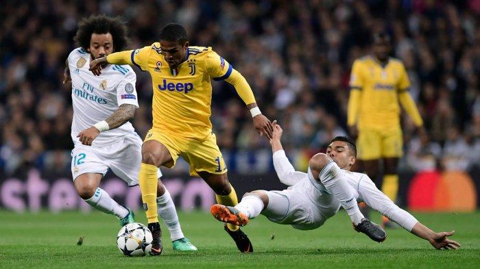 Pemain Juventus, Douglas Costa (tengah) mencoba melewati adangan dua pemain Real Madrid, Marcelo (kiri) dan Casemiro dalam laga leg kedua babak perempat final Liga Champions 2017-2018 di Stadion Santiago Bernabeu, Madrid, Spanyol, Kamis (12/4/2018) dini hari WIB.
