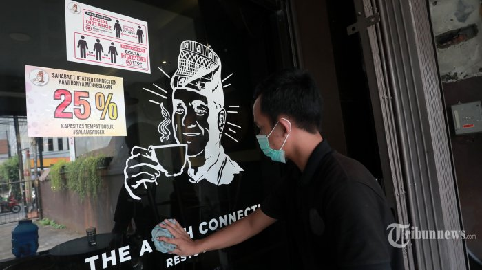 Pekerja membersihkan kaca di salah satu restoran di Jakarta, Kamis (29/7/2021). Kepala Dinas Pariwisata dan Ekonomi Kreatif (Disparekraf) DKI Jakarta, Gumilar Ekalaya mengatakan bahwa Pemprov DKI Jakarta akan mewajibkan pengunjung salon dan restoran sudah divaksin Covid-19 untuk memberikan dampak positif pariwisata di masa pandemi. Persyaratan wajib vaksin tersebut dilakukan untuk membantu program pemerintah dalam percepatan vaksinasi Covid-19. Tribunnews/Irwan Rismawan