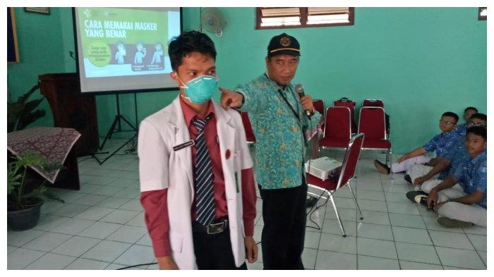Dekan Fakultas Kedokteran UNS, Reviono, memberi penjelasan berbagai macam jenis masker kepada siswa/siswi SMPN 2 Sukoharjo, Selasa (10/3/2020). (Tribunnews.com/Wahyu Gilang P)