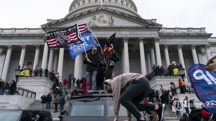 Pendukung Presiden Amerika Serikat, Donald Trump melakukan demonstrasi di luar Gedung Kongres US Capitol di Washington DC, Amerika Serikat, Rabu (6/1/2021) waktu setempat. Ribuan pendukung Presiden Amerika Serikat, Donald Trump melakukan aksi demonstrasi dengan menyerbu dan menduduki Gedung Capitol untuk menolak pengesahan kemenangan Presiden terpilih Joe Biden atas Presiden Donald Trump dalam Pemilu Amerika 2020 lalu. Mereka menduduki Gedung Capitol setelah sebelumnya memecahkan jendela dan bentrok dengan polisi. AFP/Alex Edelman