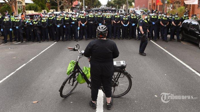 Seorang pengunjuk rasa menghadapi polisi selama demonstrasi anti-lockdown di Melbourne pada 18 September 2021. AFP/William WEST