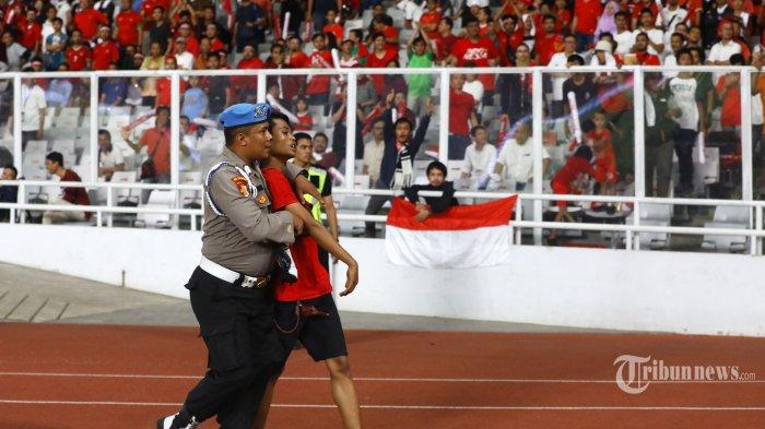 Petugas kepolisian mengamankan suporter Timnas Indonesia saat melawan Timnas Malaysia pada ajang kualifikasi Piala Dunia Qatar 2022 di Stadion Utama Gelora Bung Karno, Jakarta, Kamis (5/9/2019). Suporter Timnas Indonesia sempat masuk ke lapangan dan berbuat ricuh pada pertandingan yang dimenangkan Malaysia dengan skor 2-3. TRIBUNNEWS/IRWAN RISMAWAN