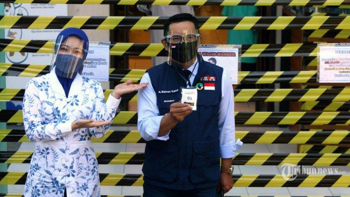 Gubernur Jawa Barat Ridwan Kamil didampingi istri Atalia Praratya mengenakan masker dan pelindung wajah memperlihatkan nomor antrean Uji Klinis Vaksin Covid-19 saat tiba di Puskesmas Garuda, Jalan Dadali, Kota Bandung, Selasa (25/8/2020). Ridwan Kamil bersama Kapolda Jawa Barat, Irjen Rudy Sufahriady dan Pangdam III Siliwangi, Mayjen TNI Nugroho Budi Wiryanto menjalani sejumlah tes kesehatan dan tes usap di Puskesmas Garuda sebagai tahapan yang harus dilakukan oleh relawan vaksin sebelum dilakukan penyuntikkan atau uji klinis tahap III Vaksin Sinovac Covid-19. TRIBUN JABAR/GANI KURNIAWAN