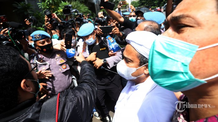 Pemimpin Front Pembela Islam (FPI), Muhammad Rizieq Shihab didampingi kuasa hukumnya, Munarman tiba di Mapolda Metro Jaya, Jakarta Selatan, Sabtu (12/12/2020). Kedatangan Rizieq Shihab untuk menjalani pemeriksaan sebagai tersangka dalam kasus pelanggaran protokol kesehatan terkait kerumunan yang terjadi di Petamburan. Tribunnews/Jeprima