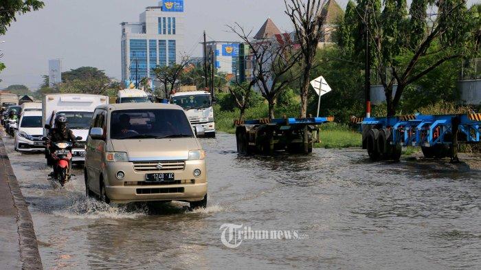 Sejumlah kendaraan bermotor berjalan perlahan saat melintasi genangan bajir rob yang menggenangi Jalan Arteri Yos Sudarso, Semarang atau jalur pantura yang menghubungkan Semarang menuju Kudus. Rabu (2/6/21).
