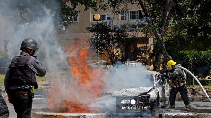 Seorang petugas pemadam kebakaran memadamkan kendaraan yang terbakar setelah roket diluncurkan dari Jalur Gaza, yang dikendalikan oleh gerakan Hamas Palestina, mendarat di kota Ashkelon di Israel selatan pada 11 Mei 2021. Israel dan Hamas saling baku tembak, dalam eskalasi dramatis antara yang pahit musuh yang dipicu oleh kerusuhan di titik nyala kompleks Masjid Al-Aqsa di Yerusalem.