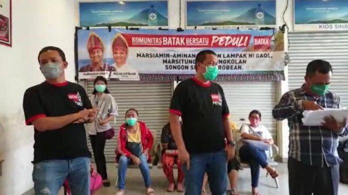 Rolas Sitinjak (paling kiri) saat membagikan paket sembako dari Komunitas Batak Bersatu (KBB) di Terminal Rawamangun, Jakarta.