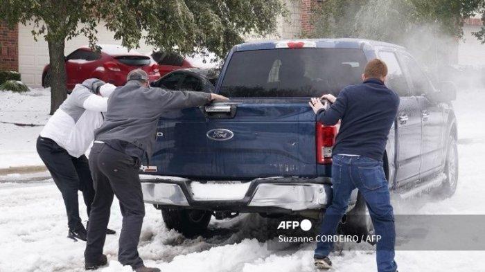 Warga membantu sopir pikap keluar dari es di jalan di Round Rock, Texas, pada 17 Februari 2021, setelah badai musim dingin menerjang