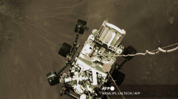 Foto yang dirilis oleh NASA ini menunjukkan rover Perseverance yang diturunkan oleh Sky Crane ke permukaan Mars pada 18 Februari 2021. NASA mengatakan pada 18 Februari 2021 bahwa rover Perseverance telah mendarat di permukaan Mars setelah berhasil mengatasi risiko yang berisiko. fase pendaratan yang dikenal sebagai