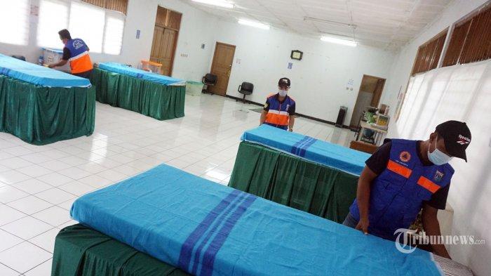 Petugas Gugus COVID-19 merapikan tempat untuk isolasi mandiri di Gedung Sasana Krida Karang Taruna RW 03, Kelurahan Pondok Labu, Cilandak, Jakarta Selatan, Rabu (10/2/2021). Penyediaan ruang isolasi mandiri ini merupakan inisiatif dari warga karna melihat angka kasus positif Covid-19 yang semakin tinggi, menurut Sekretaris RW 03, Kelurahan Pondok Labu, Moch Yahya Gedung ini disiapkan untuk antisipasi bila Wisma Atlet dan rumah sakit rujukan penuh dan Gedung ini memiliki fasilitas lima bed dengan jarak tiap bed dua meter. Kemudian wadah tempat pakaian, sendal jepit, keset, tissue serta hands sanitaiser. (Tribunnews/Jeprima)