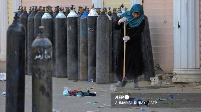 Seorang wanita Irak membersihkan puing-puing di samping botol oksigen yang dievakuasi di luar rumah di Rumah Sakit Ibn Al-Khatib di Baghdad, pada 25 April 2021, setelah kebakaran meletus di fasilitas medis yang disediakan untuk kasus virus korona paling parah. Setidaknya 23 orang tewas ketika kebakaran terjadi di unit perawatan intensif virus corona di ibu kota Irak, negara dengan infrastruktur kesehatan yang sudah lama bobrok menghadapi peningkatan kasus COVID-19.