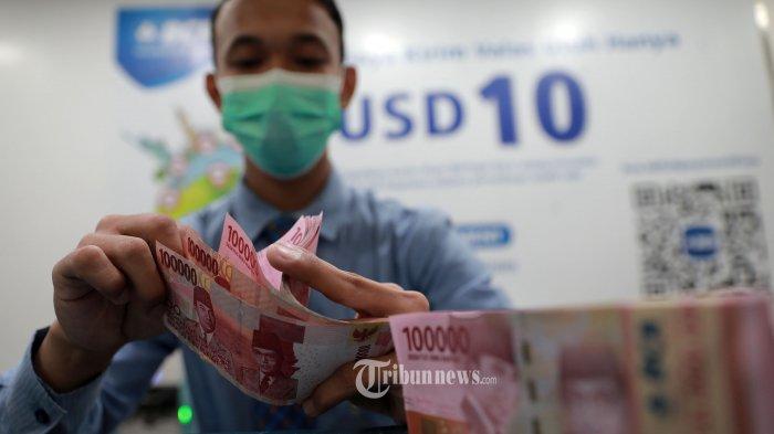 Karyawan menunjukan uang rupiah di Jakarta, Selasa (16/3/2021).