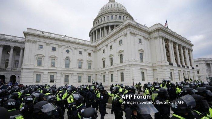 Petugas polisi berjaga-jaga saat pendukung Presiden AS Donald Trump menyerbu Capitol AS saat rapat umum untuk memperebutkan sertifikasi hasil pemilihan presiden AS 2020 oleh Kongres AS di Capitol Hill, di Washington, Amerika Serikat.