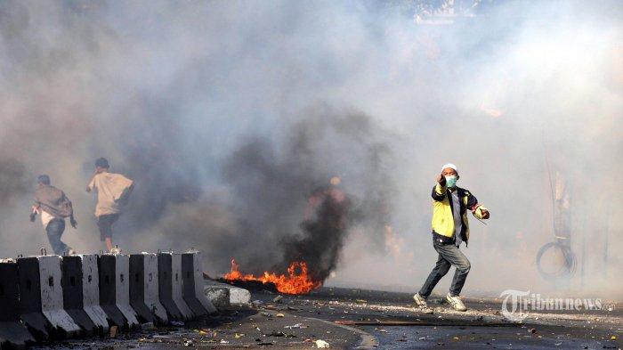 Massa melempar ke arahan polisi di Jalan Brigjen Katamso, Slipi, Jakarta Pusat, Rabu (22/5/2019). Mereka melakukan aksi pendukung salah satu pasangan capres yang menolak hasil Pemilu 2019. Warta Kota/Alex Suban