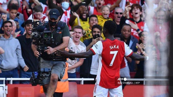 Gelandang Arsenal Inggris Bukayo Saka melakukan selebrasi di depan pendukungnya setelah mencetak gol ketiga mereka dalam pertandingan sepak bola Liga Inggris antara Arsenal dan Tottenham Hotspur di Stadion Emirates di London pada 26 September 2021.