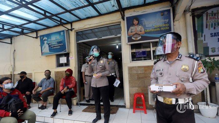 Petugas Polisi memakai alat pelindung diri (APD) saat melayani warga yang ingin melakukan kepengurusan Surat Izin Mengemudi (SIM) di Samsat Jakarta Timur, Kamis (4/6/2020). Samsat Jakarta Timur menerapkan protokol kesehatan untuk mencegah penyebaran virus corona (Covid-19) sejak dibukanya kembali pelayanan kepengurusan SIM dan STNK. Tribunnews/Herudin