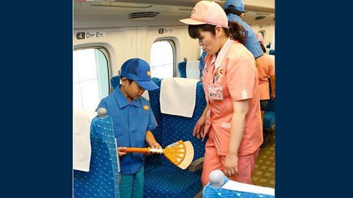 Seorang pelajar sekolah dasar di Jepang sedang mencoba menggunakan sapu ajaib Shinkansen.