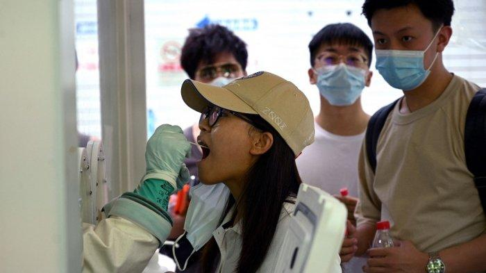 Sampel swab diambil dari seorang wanita untuk diuji virus corona Covid-19 di sebuah rumah sakit di Beijing pada 2 Agustus 2021, di tengah wabah virus corona paling luas di negara itu dalam beberapa bulan.